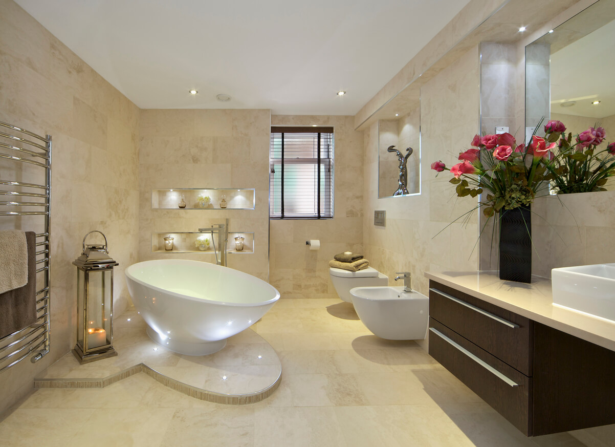 a modern bathroom in an expensive new home with a tear-drop shaped bath (full of water) sitting on a marble plinth. A bidet and WC are located near the window. A lantern with lit candles sits next to a large towel rail whilst a large bunch of red lilies sit on the cabinet to the right of the picture.