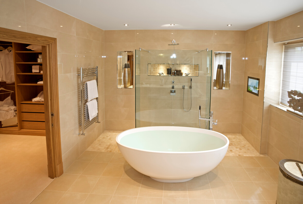 an elegant master bathroom in an expensive new luxury home. An unusual oval bath full with hot water sits in the middle of the room.  The decor has been tastefully prepared by a leading Interior Designer.
