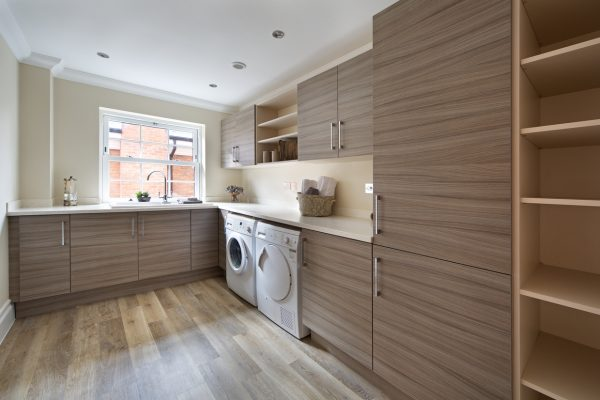 a lovely utility room in a large modern new home with ample cupboard space, work-top space and separate washing machine and dryer. The flooring is a high quality porcelain oak-wood effect tile which looks completely natural. The room has been lightly dressed for this image.
